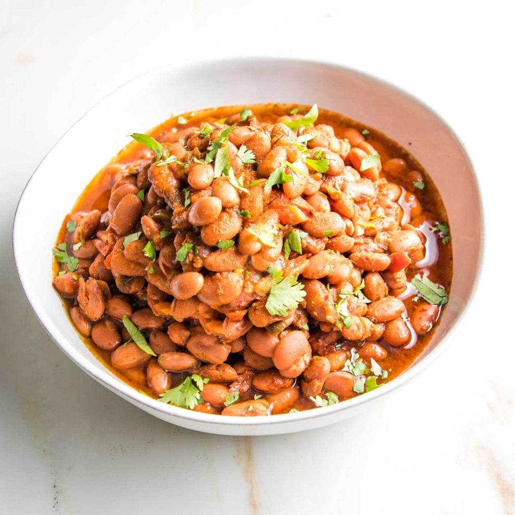 Close up of a white bowl filled with mexican style pinto beans in tomato sauce with chopped cilantro sprinkled on top.