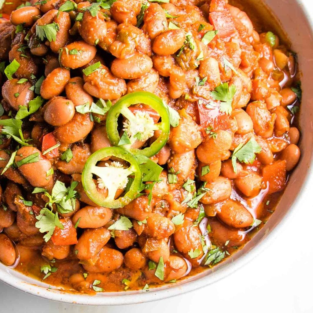 Mexian Style pinto beans in tomato sauce, garnished with sliced jalapenos and sprinkled with fresh chopped herbs