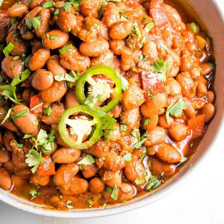 Close up of a white bowl of pinto beans in a tomato based sauce, topped with jalapeno slices and sprinkled with cilantro