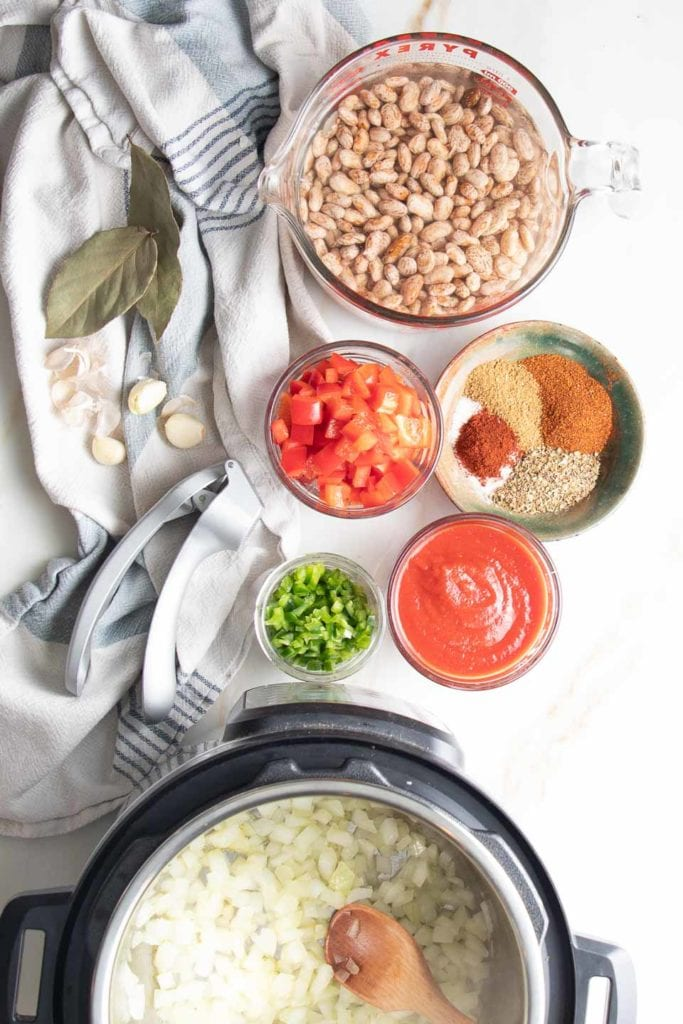 Instant Pot Mexican Beans step one saute the onions. PHoto shows remaining ingredients standing by.