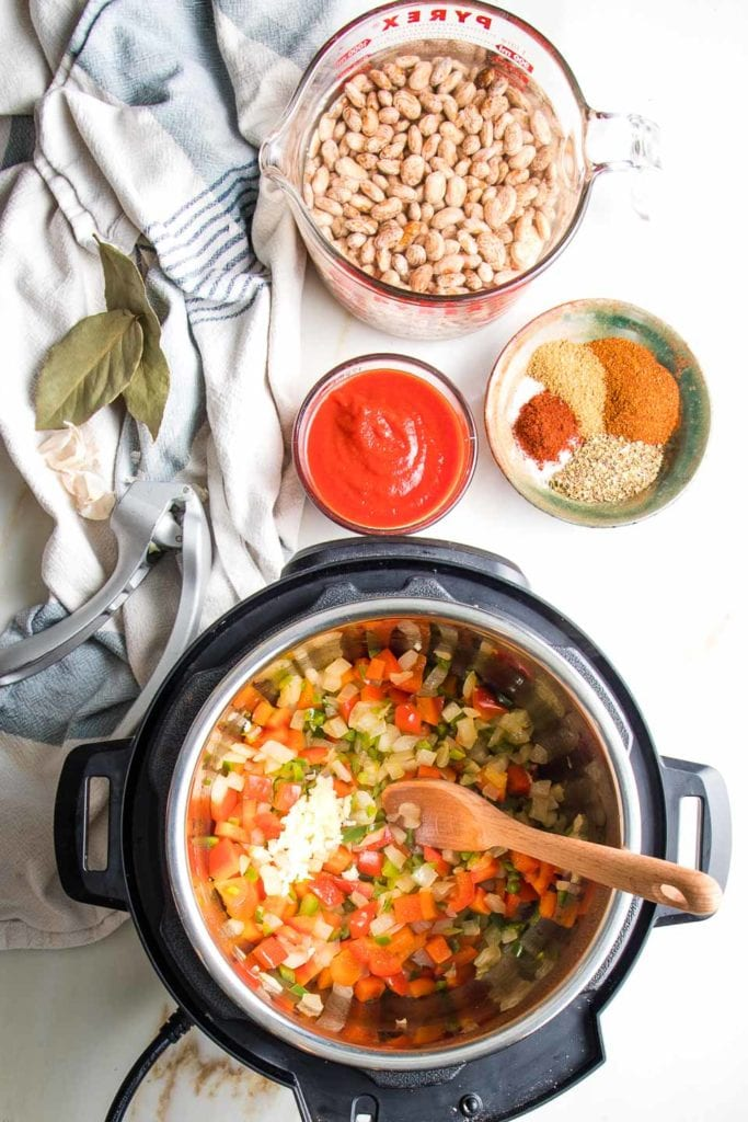Instant Pot with sauteed veggies and garlic, dried beans plus tomato sauce and spices wiating on the stide.