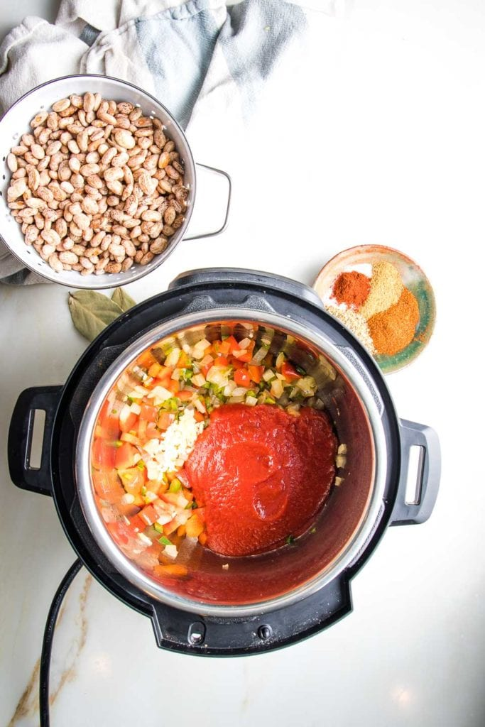 Instant pot with sauteed veggies plus garlic and tomato sauce, dried beans and spices on the side.
