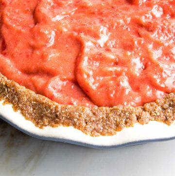Close up of no bake strawberry pie filling inside nut crust in a ceramic pie plate.