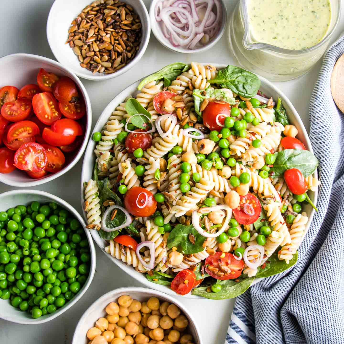 A white bowl filled with pasta salad and small bowls of the ingredients surrounding it: chick peas, green peas, halved cherry tomatoes, sunflower seeds, shallots and tahini parsley dressing.