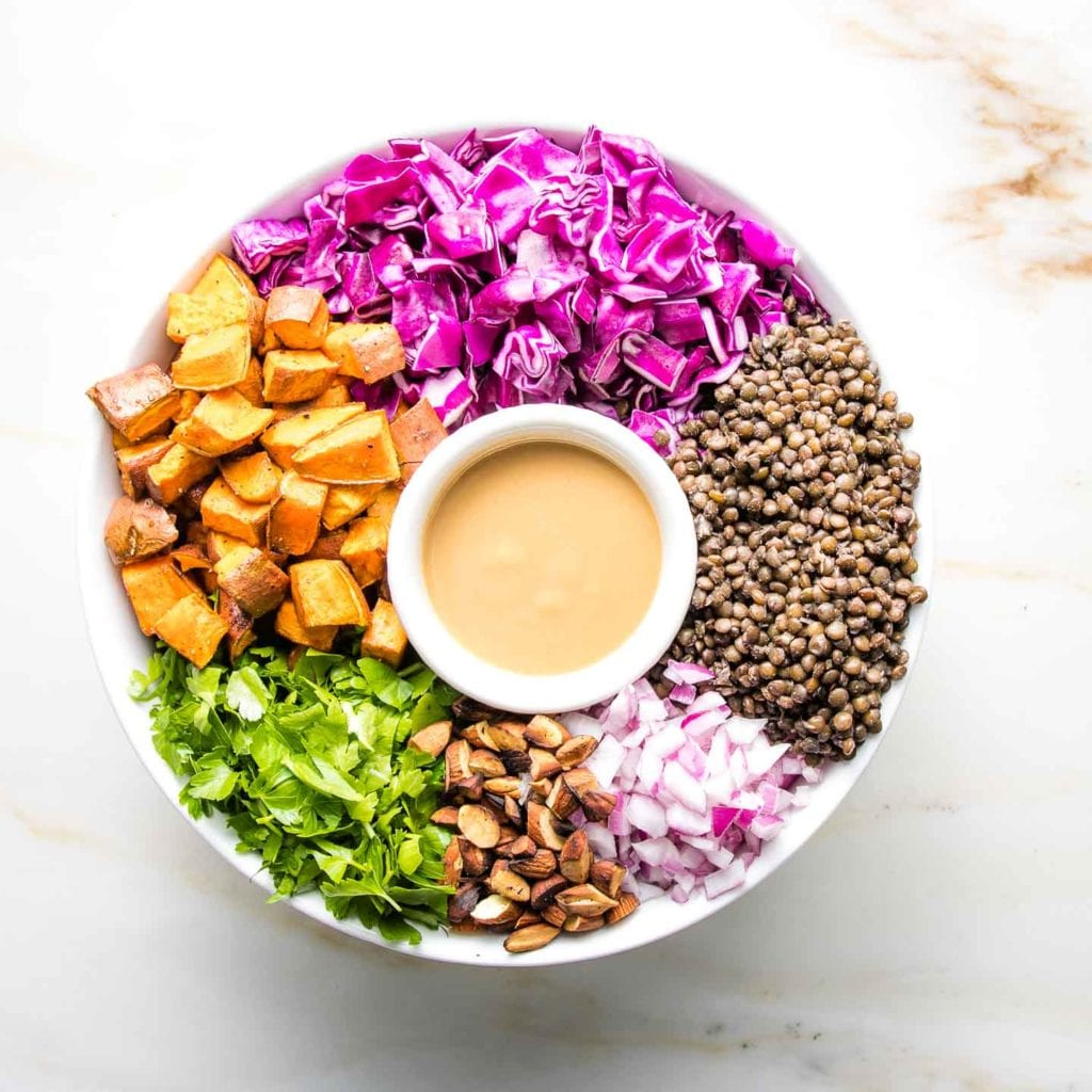 Vegan Lentil Salad with colorful ingredients arranged around a small dish of dressing.