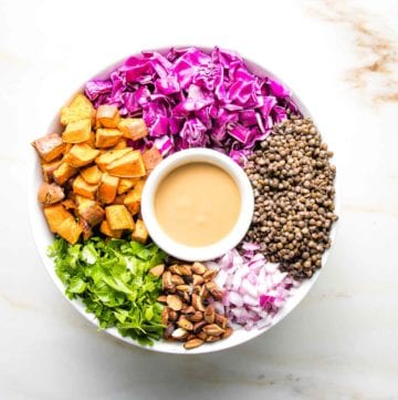 white bowl filled with sweet potatoes, cabbage, lentils, onions, almonds, parsley around a small bowl of dressing
