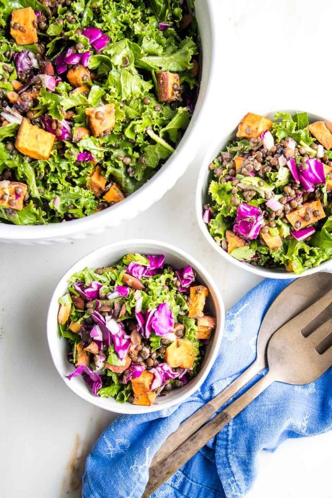 large bowl of colorful lentil salad and two smaller bowls loaded with purple cabbage, , orange sweet potatoes, black lentils, almonds and onions.