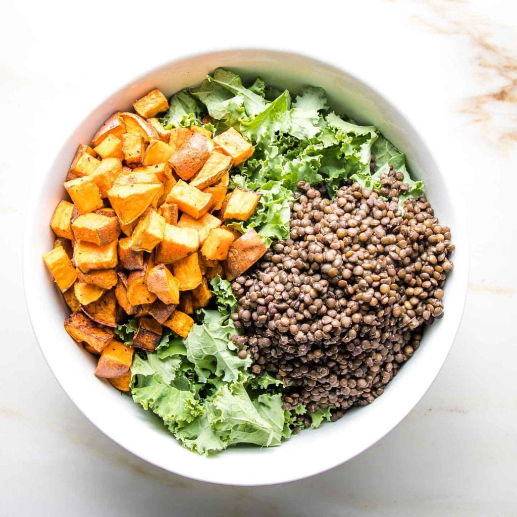 Large white bowl filled with kale plus black lentils and roasted sweet potato cubes.