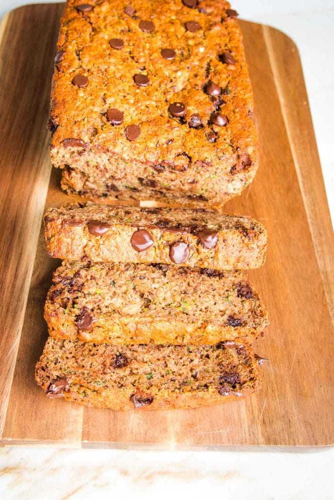 Super moist and healthy chocolate chip zucchini bread slices on a wood grained cutting board.