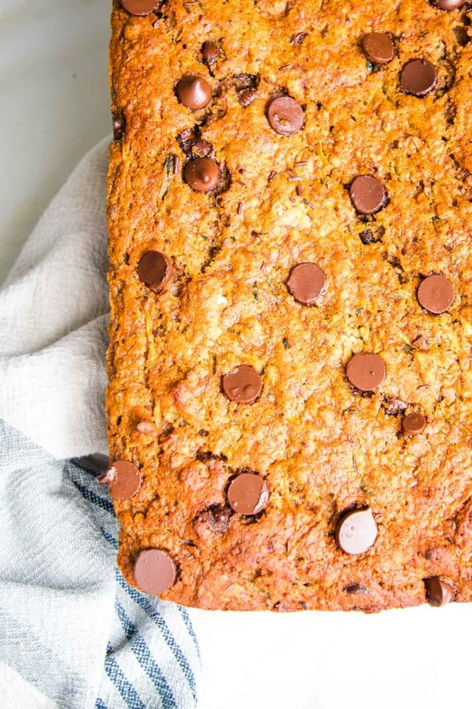A loaf of healthy and moist zucchini bread with chocolate chips cooling on a cotton tea towel.