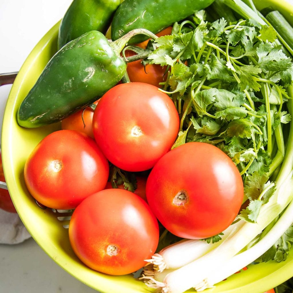 A light green collander filled with fresh tomatoes, jalapenos, scallions and cilantro.