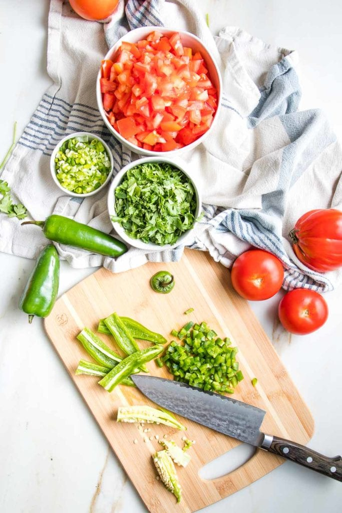Fresh chopped tomatoes, cilantro and scallion for salsa, along with a cutting board with knife, showing how to remove the seeds and membranes from the jalapeno to chop.