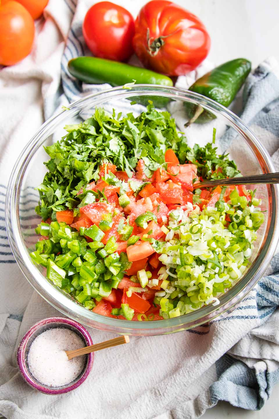 Chopped tomatoes, jalapenos, scallions and cilantro in a glass bowl with a small dish of salt and more raw veggies around it.
