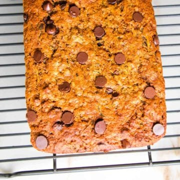 Chocolate Chip Zucchini Bread cooling on a wire rack on a white countertop.