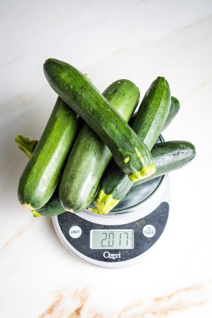 6 zucchini on a scale to show what 2 lbs of zucchini looks like.