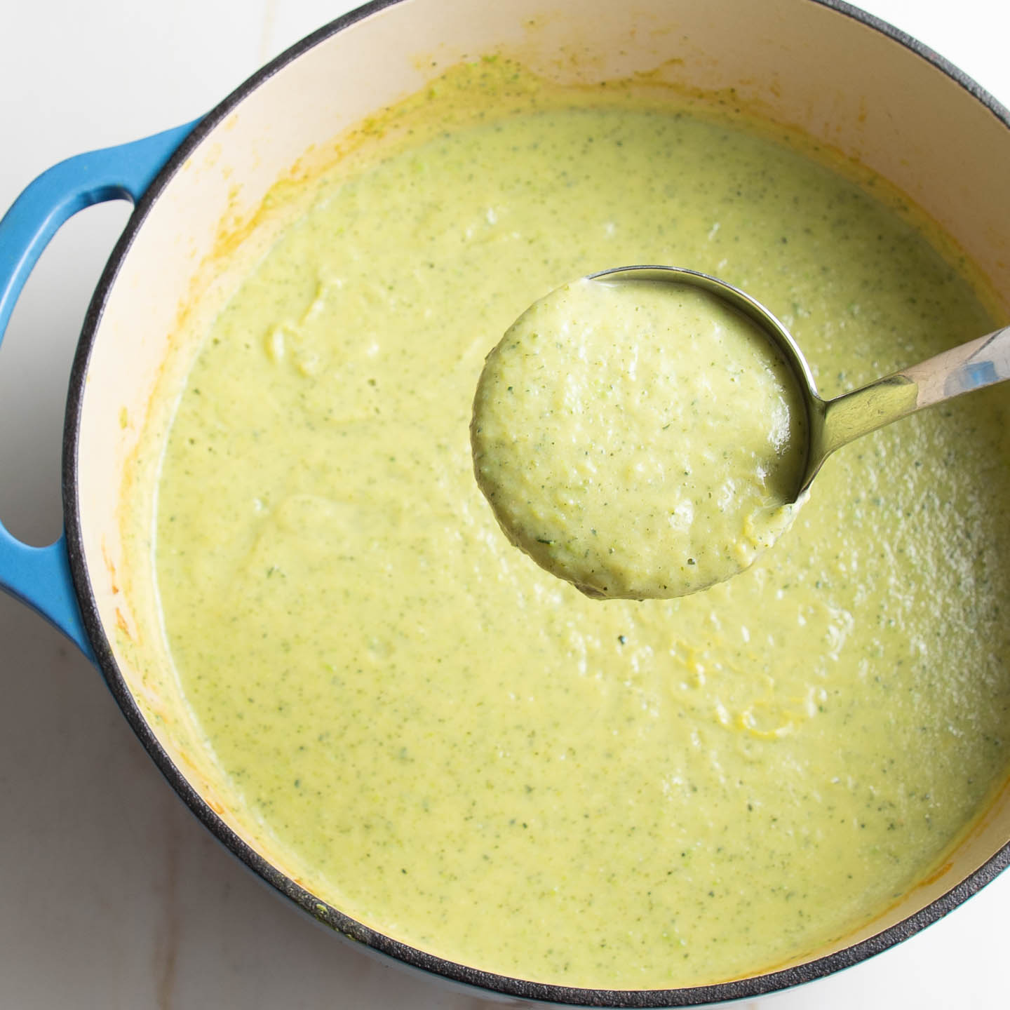 Thick and creamy light green zucchini soup shown on a ladle coming out of a pot.