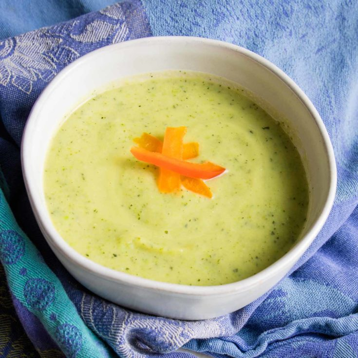 White bowl on a blue towel filled with light green creamy zucchini soup and sprinkled with thin red pepper strips