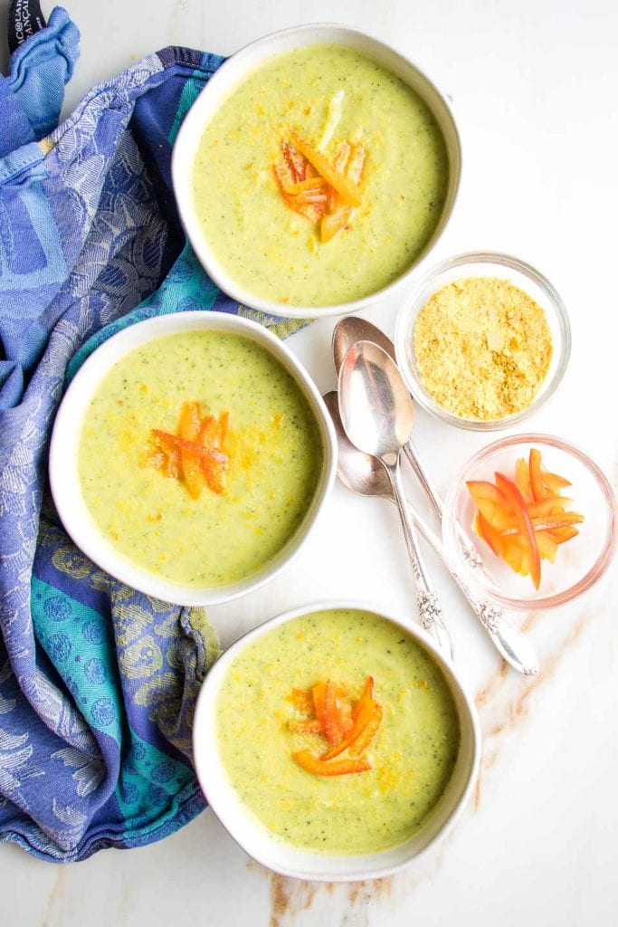 Three white bowls, filled with light green creamy zucchini soup and sprinkled with nutritional yeast and strips of red pepper on a white background with a blue tea towel.