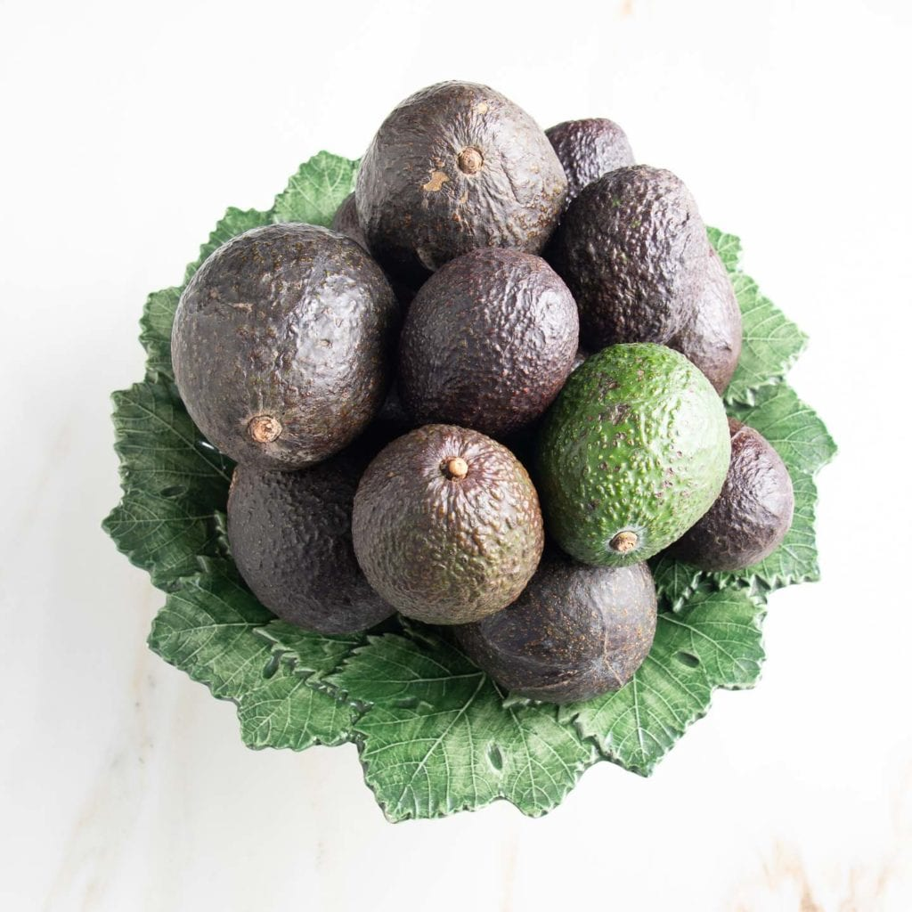 A green leaf ceramic plate with a heaping pile of avocados of various colors and sizes.