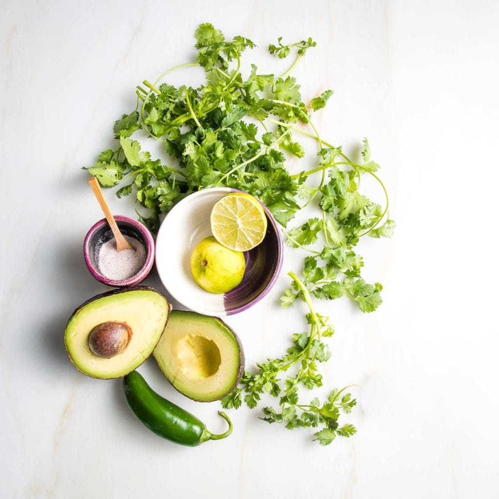 Beautifully arranged ingredients for avocado dressing: cilantro, lime, jalapeno, perfectly ripe avocado split open, small ceramic dish with sea salt and a tiny wooden spoon.