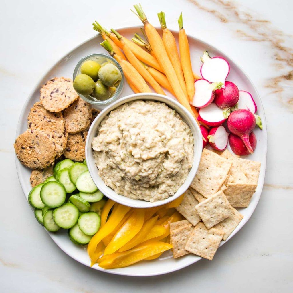 Round white plate with crackers, olives, carrots, radish, bell pepper slices and cucumber rounds with a bowl of baba ganoush in the center for dipping.