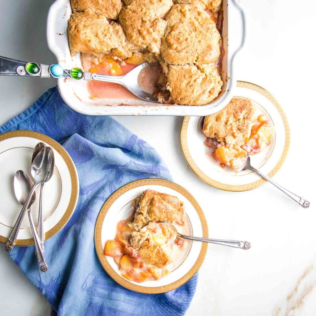 Square pan filled with peach cobbler and a large serving spoon scooping it out onto white plates with gold trim.  The cobbler on the plate is filled with sliced peaches in a thick sauce with pieces of topping intermixed