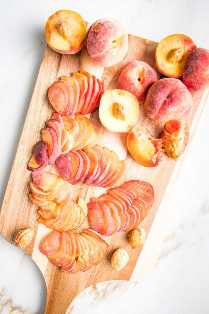 Fresh Peaches on a cutting board, cut into halves. Then slices.