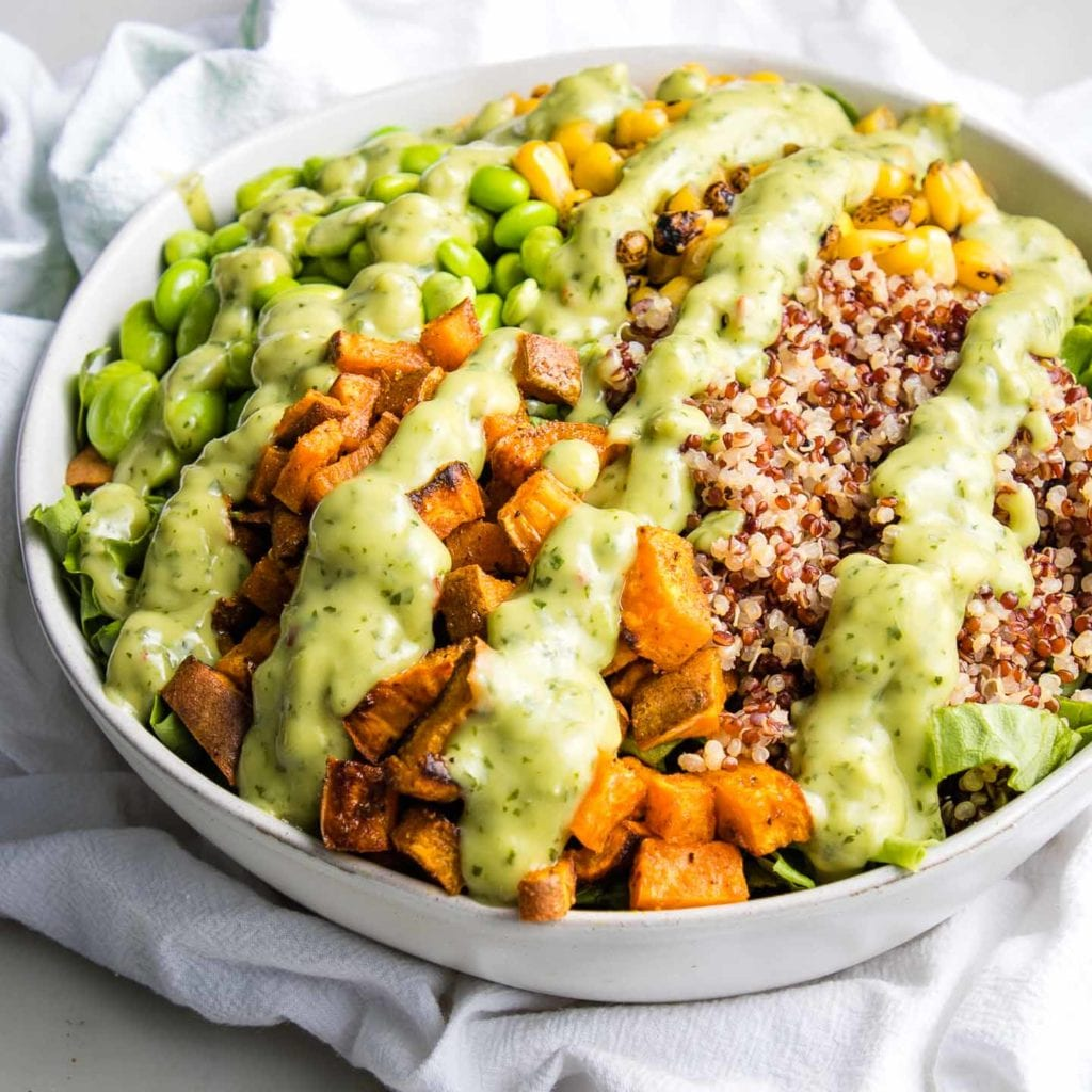 White bowl filled with greens, roasted sweet potatoes, quinoa, edamame beans and corn, drizzled with avocado lime cilantro dressing