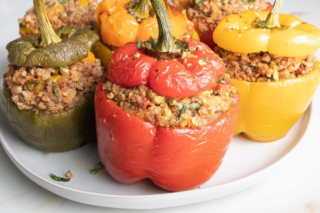 Vegan Stuffed Peppers in green, yellow, orange and red.  Filled with quinoa, lentils and Italian spices.