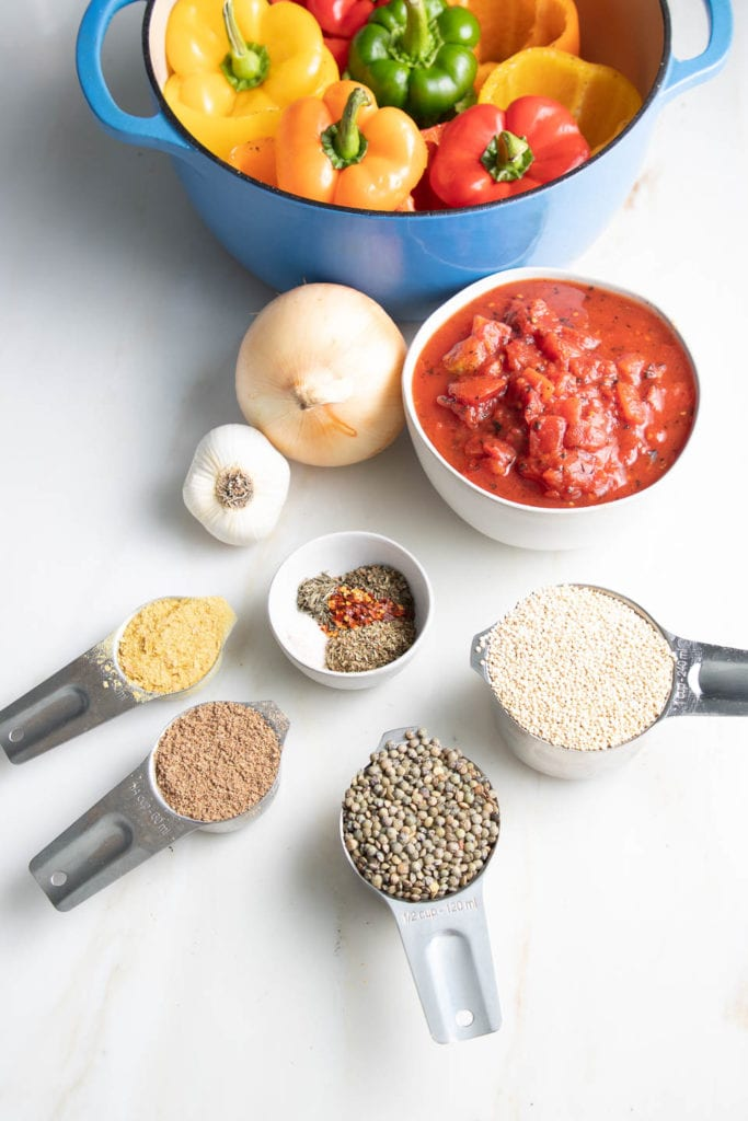Ingredients for vegan stuffed peppers: colorful bell peppers, diced tomatoes, quinoa, lentils, onions, garlic, Italian spices, ground flax and nutritional yeast.