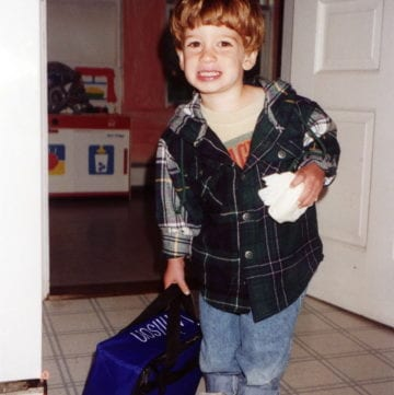 A little boy with a lunch box.