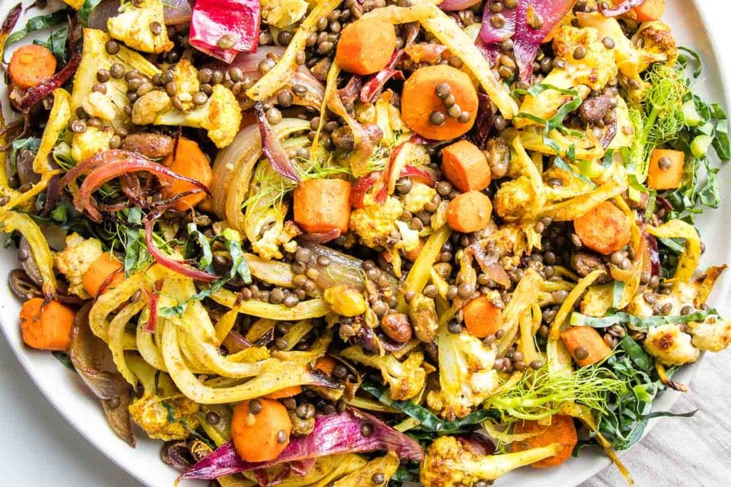 Bright, colorful roasted red onions, carrots, fennel and cauliflower mixed with lentils, pistachios and raisins in a large white bowl.