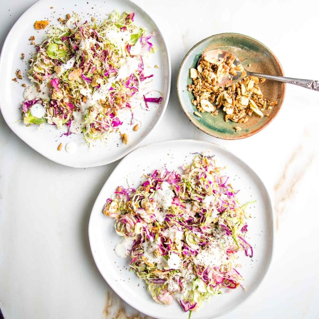 Brussels Sprouts Salad on two white plates with colorful red cabbage, drizzled with a creamy, dairy-free dressing and some toasted nuts/seeds with a little bowl of nuts and seeds and a spoon.