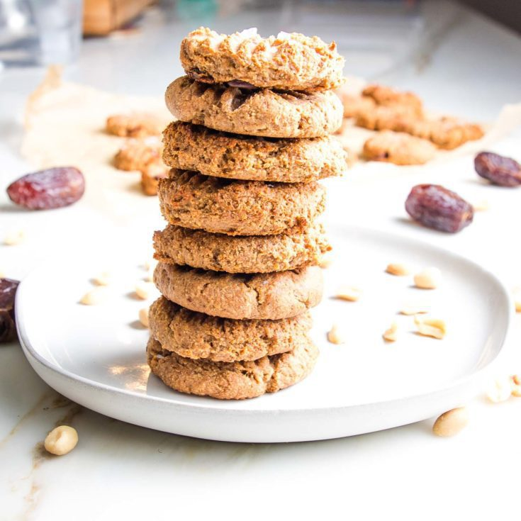 A stack of peanut butter cookies on a white plate, surrounded by peanuts, dates and more cookies.