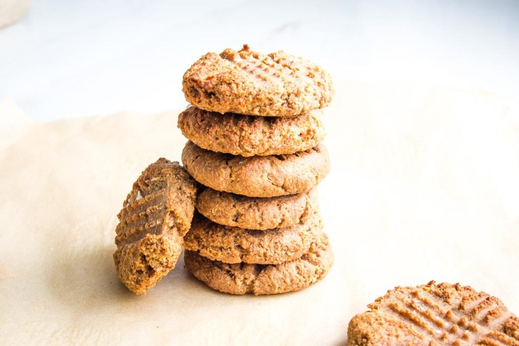 One peanut butter cookie leaning on a stack of 6 piled onto each other and one other cookie in the foreground.