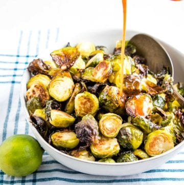 A stream of sweet and spicy sauce being poured onto a white bowl filled with crispy oven roasted brussels sprouts. There's a lime in the foreground and a teal striped towel underneath the bowl.