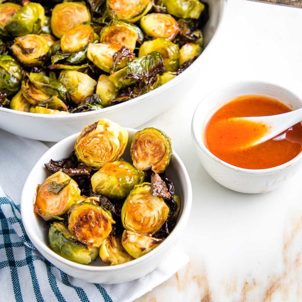 Serving bowl of crispy brussels sprouts, along with an individual bowl of sprouts drizzled with a sweet and spicy sauce and a small bowl with a spoon of extra honey-lime-sriracha sauce.