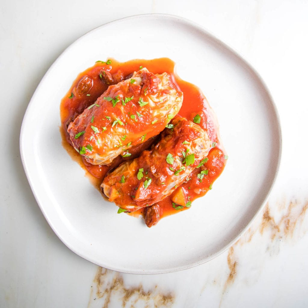 round plate with two hefty stuffed cabbage rolls and sauce spooned over.