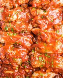 close up of vegan stuffed cabbage rolls in a white baking dish. Cabbage leaves stuffed with lentils, cauliflower rice and spices, topped with sweet and sour sauce and baked until soft and tender.