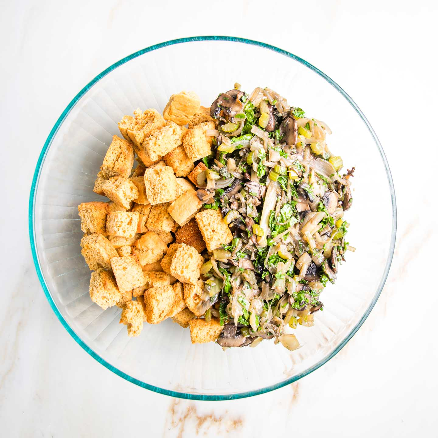 Cornbread croutons plus sauteed veggies and herbs in a large glass bowl.