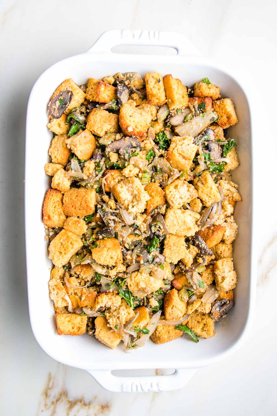 White rectangular baking dish filled with cornbread croutons mixed with sauteed veggies and soaked with veggie stock.