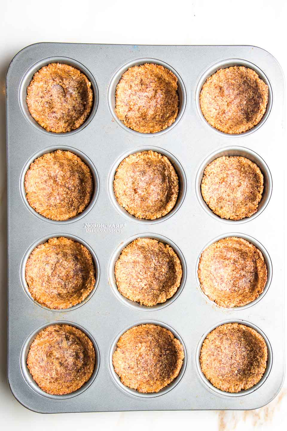 Muffin tins filled with pre-baked gluten-free pumpkin pie crusts.