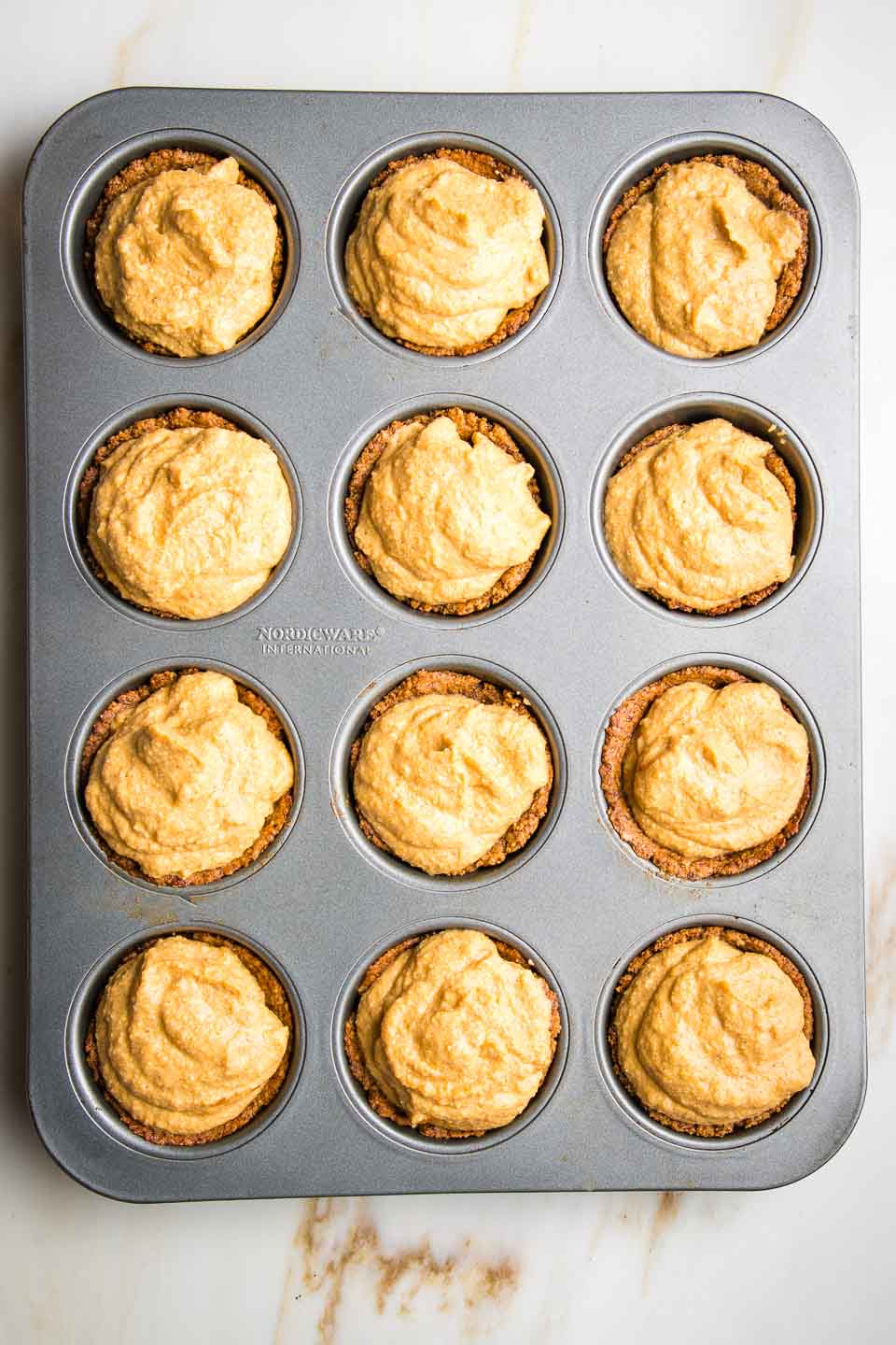 Mini Pumpkin Pies filled into muffin tins and ready to bake.