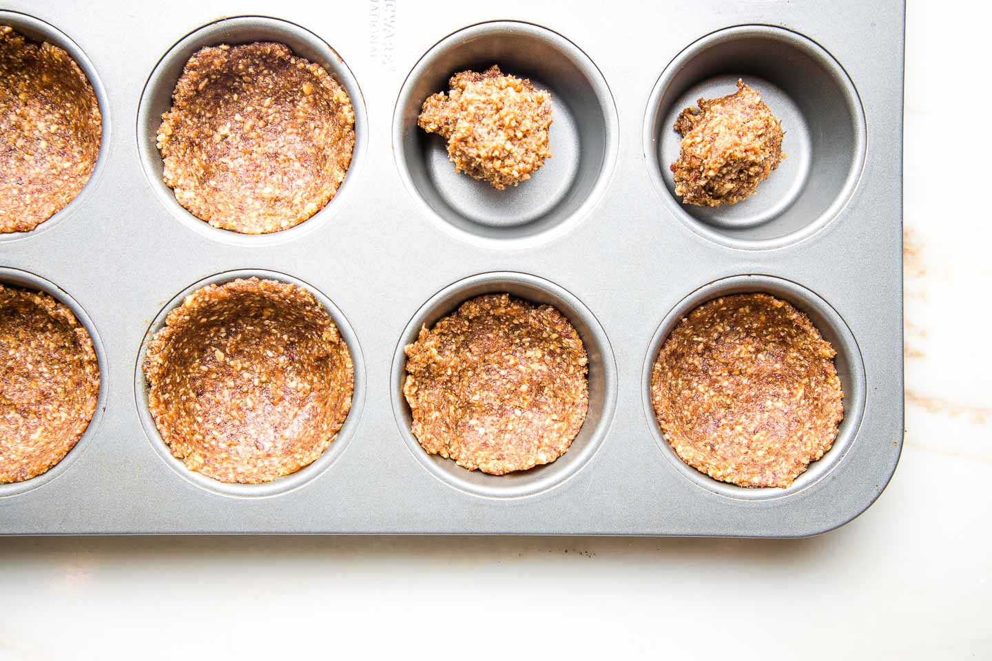 Muffin tin filled with gluten-free crust in heaps and some are pressed flat against the bottom and up the sides.