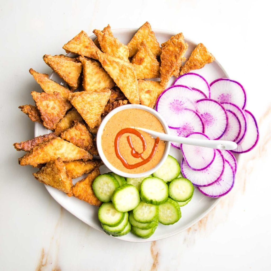 Crispy baked tofu, plus sliced purple radishes and cucumbers on a round white plate. A small dish of almond butter sauce is in the center with a swirl of sriracha.