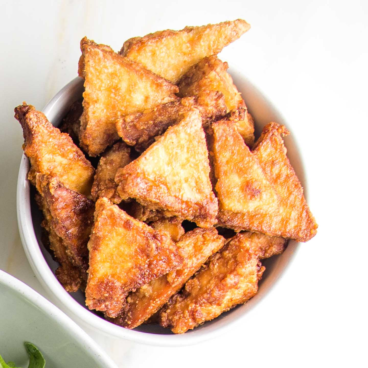 small white bowl filled with crispy baked tofu triangles