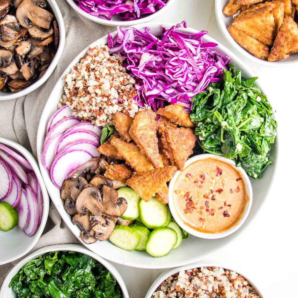 Bowls filled with sauteed mushrooms, sliced purple radishes, crispy tofu, quinoa, garlicky spinach and shredded cabbage. A white bowl filled with some of each plus a dish of almond butter dressing sprinkled with chopped almonds and crushed red pepper.