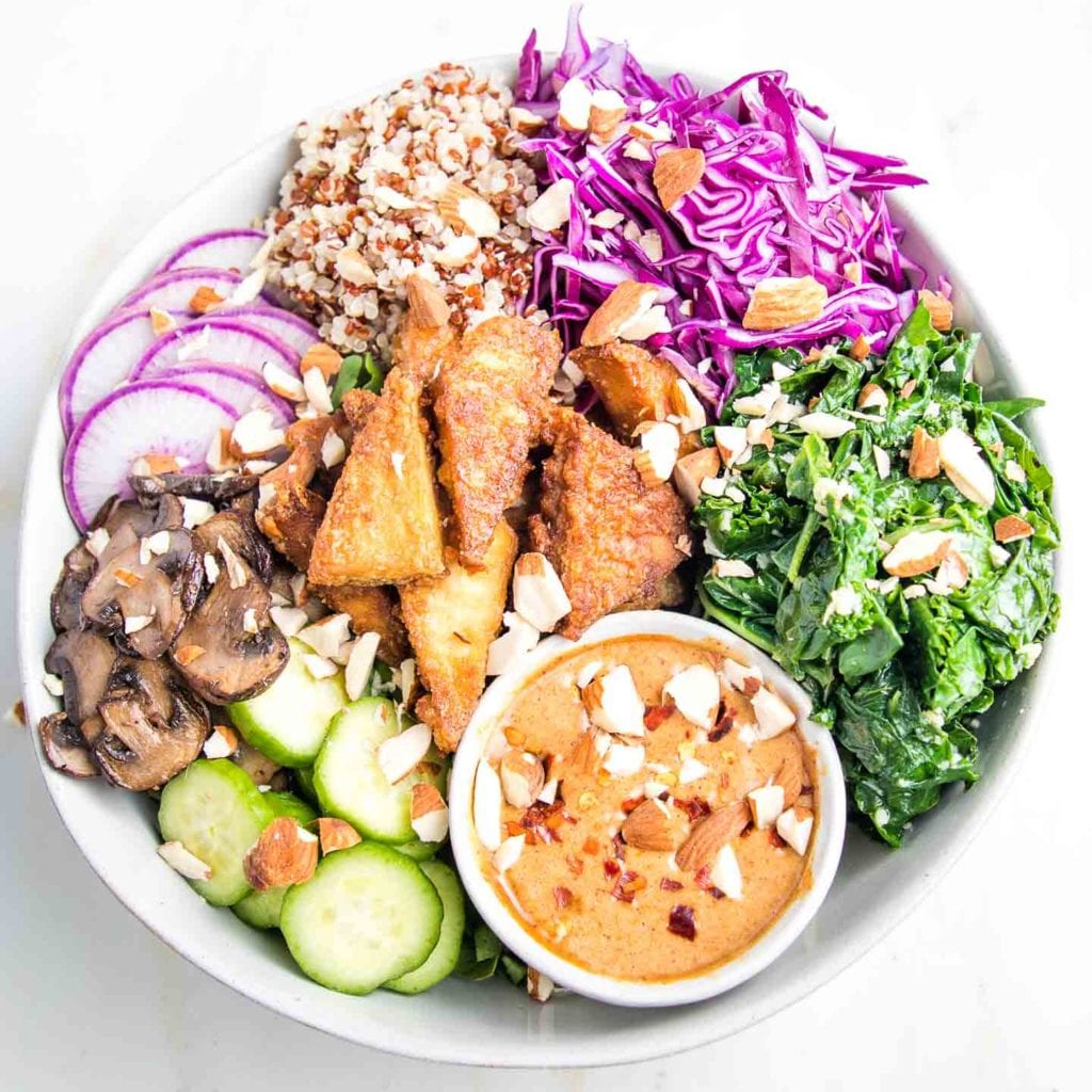 White bowl filled with browned, crispy tofu and brightly colored vegan assortment. Sauteed mushroom slices, sliced purple radishes and cucumbers, tri-color quinoa, shredded red cabbage, bright garlicky greens and a small dish of almond butter dressing with chopped almonds and crushed red pepper.