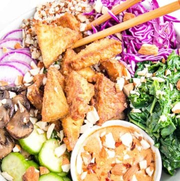 Close up of a brightly filled bowl of vegan food. Crispy triangles of tofu, sliced purple radishes, bright garlicky greens, sauteed mushrooms, tri-color quinoa, and a small bowl of almond butter dressing. Chopped almonds scattered over everything.