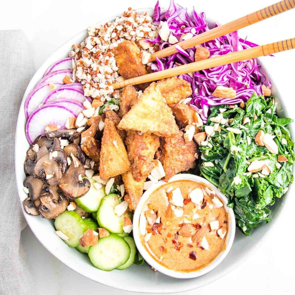 Brightly colored food in a white bowl with some chopsticks picking out a piece of crispy tofu. There is also a scoop of quinoa, some shredded red cabbage, some garlicky wilted kale, sauteed sliced mushrooms, sliced purple radish and cucumbers and a dish of almond butter dressing.